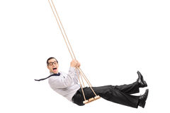 Delighted young man swinging on a swing. And looking at the camera isolated on white background Royalty Free Stock Image