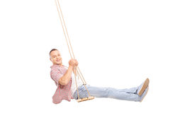 Delighted young man swinging on a wooden swing. Profile studio shot of a delighted young man swinging on a wooden swing and looking at the camera isolated on Royalty Free Stock Photography