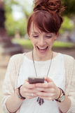 Delighted young woman reading an sms on her mobile Royalty Free Stock Photos