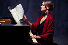 Free Delighted Young Woman Turning The Sheet Music With Notes While P Royalty Free Stock Photos - 80087428