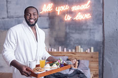 Delightful African American man holding breakfast tray in the bedroom Stock Images