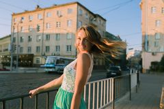 Delightful blonde woman with charming smile posing at the sunris. Delightful young  blonde woman with charming smile posing at the sunrise and sun glare Stock Photo