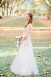 Delightful bride stands on fallen leaves in autumn park Royalty Free Stock Photos