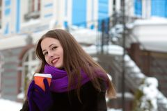 Delightful brunette model dressed in warm coat and scarf and dri. Delightful young woman dressed in warm coat and scarf and drinking tea at the street Stock Photography