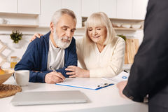 Delightful elderly couple signing documents at home. Our important day. Smiling involved delighted elderly couple sitting at home and having meeting with broker royalty free stock image