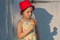 The delightful girl in a red hat eats ice cream Stock Photo