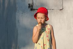 The delightful girl in a red hat eats ice cream Stock Photos