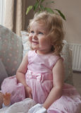 Delightful laughing baby girl on a sofa. Smiling baby girl,  nearly two years old, on a sofa with cushions at home, in a pink dress posing for the camera with Royalty Free Stock Photography