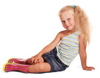 Delightful little blond girl in rubber boots sitting isolated. Stock Photos