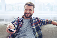 Delightful male in checkered shirt switching channel with remote. Close-up of delightful male in checkered shirt switching channel with remote control Royalty Free Stock Image