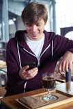 Delightful male surfing in mobile phone sitting over cup of coff Royalty Free Stock Image