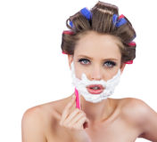Delightful Model In Hair Curlers Posing With Razor Royalty Free Stock Photography