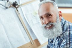 Delightful old bearded man is expressing gladness. Feeling happy. Close-up of face of cheerful senior gray-haired engineer is looking at camera with wide smile royalty free stock photography
