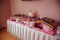 Delightful pieces of cut cakes stand on the pink buffet Royalty Free Stock Photo