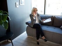 Delightful senior businesswoman is expressing gladness. Successful and rich. Top view of cheerful attractive gray-haired elegant woman is sitting on couch with stock photos