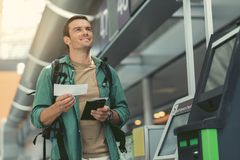 Delightful traveler is waiting for flight. Feeling of joy. Positive adult man with backpack is standing at modern airport and holding his boarding pass while Stock Photo