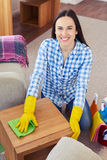Delightful woman cleaning with mop small coffee table Stock Photography