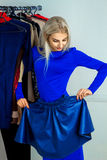 Delightful young blond woman trying on a skirt Stock Photography