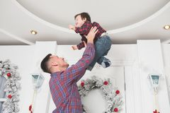 delightful young man throw up his little child in christmas decor interior stock photos