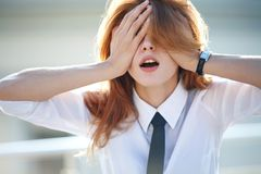 Delightful young woman closed her eyes with both hands Stock Photography