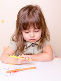 Delighting drawing girl at the desk in preschool Royalty Free Stock Photos