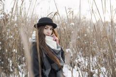 Delikat brunettflicka i vinterlandskap bland visset högt gräs Stilfull plommonstop och halsduk Allt täcker vid snö royaltyfria foton