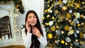 Delikat gullig kvinnlig som talar på telefonen i förväntan av det nya året och in sitter på bakgrund av träd och brand arkivfilmer