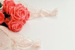 Delikat kvinnligt tema Rosa korallrosor tenderar färg på ett blekt - den rosa behå- och pärlahalsbandet på en vit bakgrund Top be royaltyfri bild