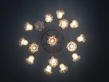 Delikat ljuskrona med lampor i blommaformat från ner upp Arkivfoto