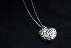 Delikat silverhjärta på svart backgound Arkivfoto