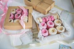 Delikata kräm- och rosa marshmallower som packas i askar av kraft papper royaltyfri foto