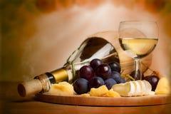 Delikatessenhintergrund - Wein, Käse, Trauben Stockfotografie