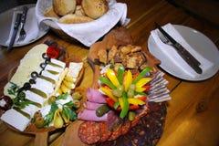 Delikatessennahrung auf einer hölzernen Platte Lizenzfreie Stockfotografie