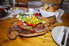 Delikatessennahrung auf einer hölzernen Platte Lizenzfreies Stockbild