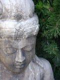 Delikatna wietrzejąca cementowa statua Buddha w repose obramiającym sosnowymi igłami Zdjęcia Royalty Free
