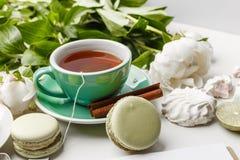 Delikatne białe peonie z herbatą, cytryną, dojrzałymi truskawkami i ciastkami na białym stole, obrazy royalty free