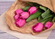 Delikatny różowy wiosna bukiet tulipany w pakunku Kraft papier na papierze Obrazy Stock