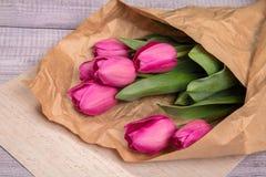 Delikatny różowy wiosna bukiet tulipany w pakunku Kraft papier na papierze Obraz Stock