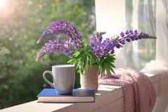 Delikatny skład z purpurowym lupines bukietem, filiżanką i książką, Zdjęcie Stock