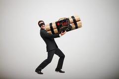 Delinquente de riso na máscara preta que leva a bomba grande imagens de stock