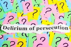 Delirio del testo di sindrome di persecuzione sulle note appiccicose variopinte contro lo sfondo dei punti interrogativi Fotografia Stock