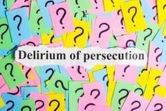 Delirium van de tekst van het vervolgingssyndroom op kleurrijke kleverige nota's tegen de achtergrond van vraagtekens stock fotografie