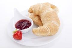 Deliscios新鲜的新月形面包用查出的草莓酱 免版税图库摄影