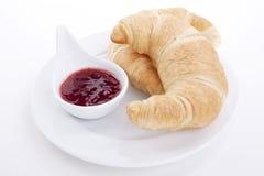 Deliscios新鲜的新月形面包用查出的草莓酱 库存图片