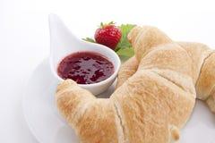 Deliscios新鲜的新月形面包用查出的草莓酱 库存照片
