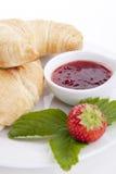Deliscios新鲜的新月形面包用查出的草莓酱 免版税库存图片
