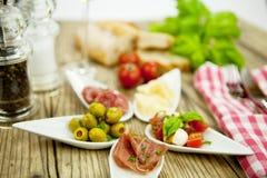 Deliscious开胃小菜板材用帕尔马巴马干酪橄榄 免版税库存图片