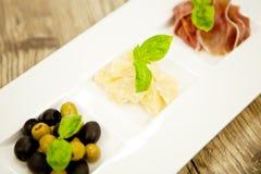 Deliscious开胃小菜板材用帕尔马巴马干酪橄榄 免版税图库摄影