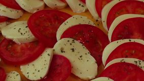 Delisious salad  with mozzarella cheese and sliced tomatoes decorated with basil stock video footage