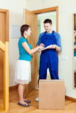Delivary man in uniform delivered a box to young woman Royalty Free Stock Photo